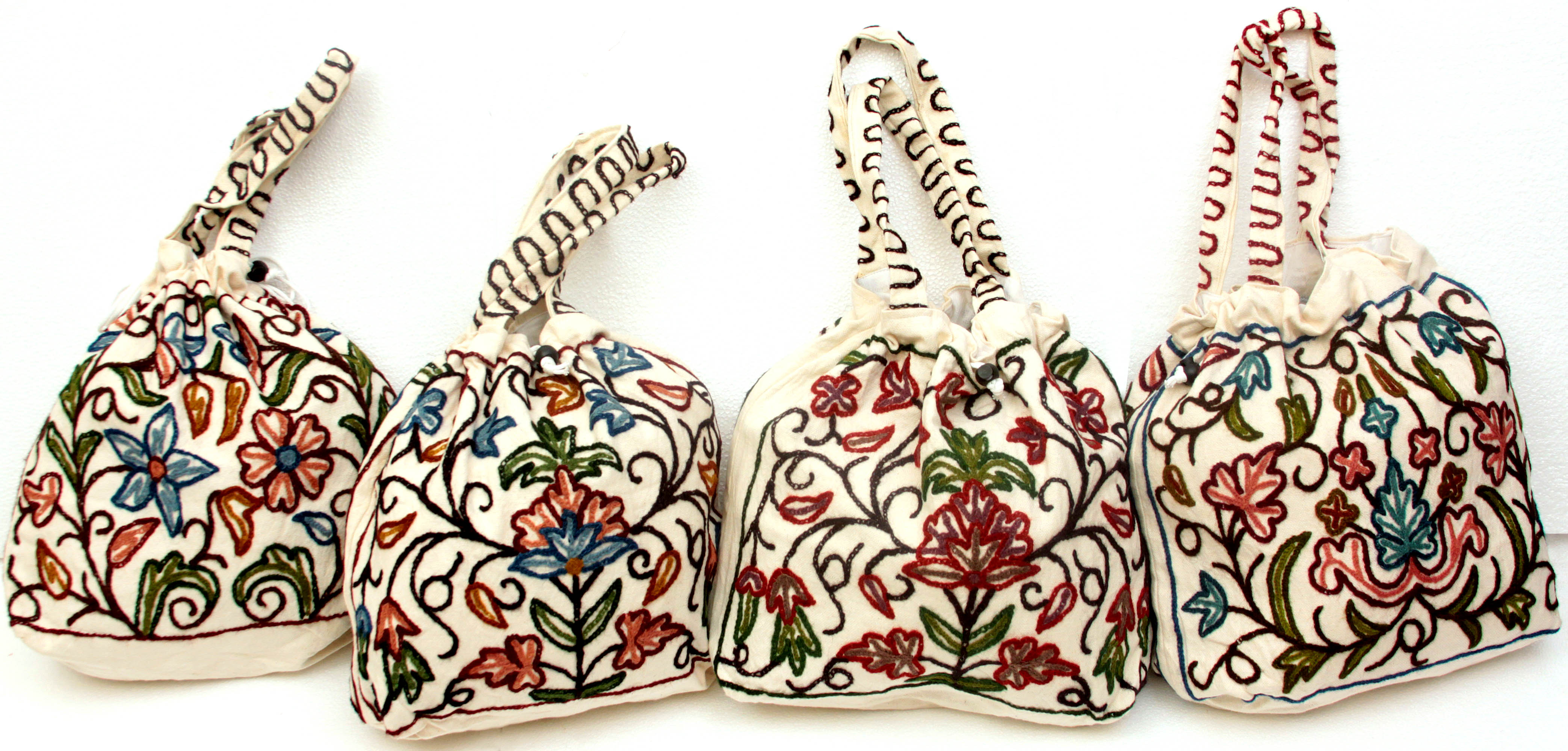 Lot of four drawstring shoulder handbags with crewel